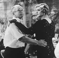 Billy Wilder shows Jack Lemmon how to cut a rug in full Daphyne garb